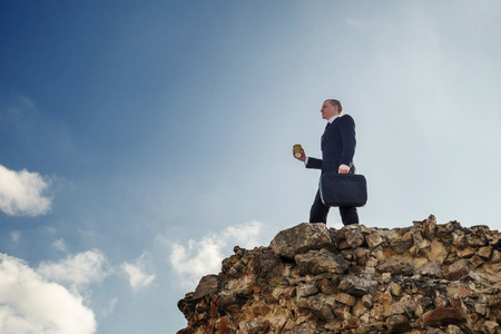 Young businessman standing on a peak. Success winner. Leader concept