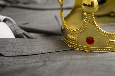 Gold crown lying on the suit of a businessman. Business concept. Metaphor