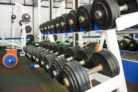 Rows of dumbbells in the gym. Dumbbells on the rack in the sports hall of the club