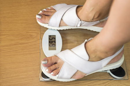 Female feet with weight scale on wooden floor. A pair of female feet standing on a weight scale