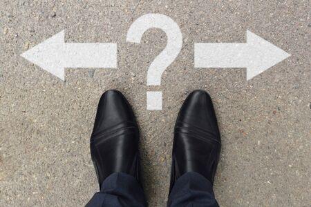 Pies de hombre de negocios en zapatos de pie sobre las marcas de la carretera de asfalto con flechas apuntando a izquierda y derecha con signo de interrogación. Par de pies de pie en la carretera asfaltada con flechas y signo de interrogación