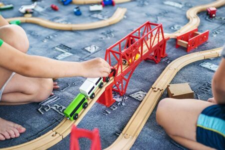 Child play with wooden train, build toy railroad at home or kindergarten. Toddler kid play with wooden train Stock Photo