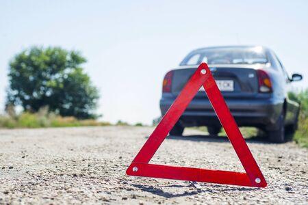 Czerwony trójkąt ostrzegawczy z uszkodzonym samochodem. Czerwony znak stopu awaryjnego i zepsuty samochód na drodze