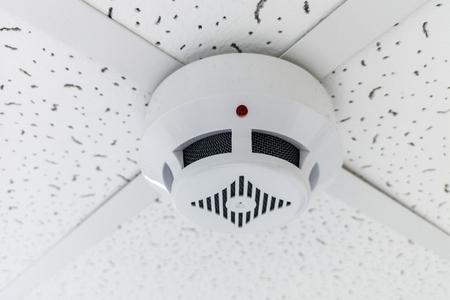 Modern smoke sensor hanging on ceiling. Temperature gage circular wall.The wall of the smoke sensor on the ceiling of the circular Stock Photo