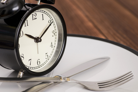 Alarm clock on plate with knife and fork on wooden background. Time to eat. Weight loss or diet concept Foto de archivo