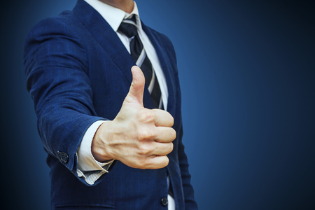 Businessman shows thumb up sign gesture. Nonverbal communication. Like, OK, perfect, good job, praise, satisfied, thumb up gesture of businessman