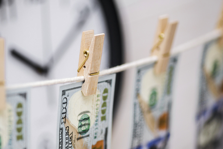 US dollar banknotes hanging on rope on clock background for money laundering concept