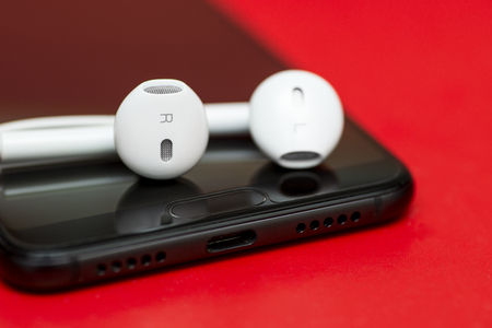 Smartphone with earphones on color background. Smartphone and earphone on red background. Close-up of smart phone with headphones on a red background Imagens
