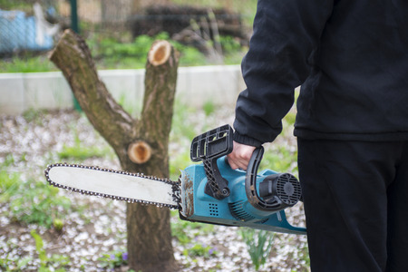 Man in black clothes hold blue chainsaw with his bare hands. Stock Photo