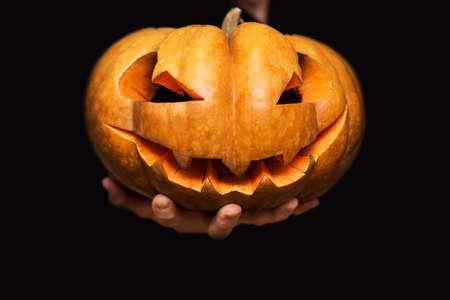 Hand shows halloween pumpkin from darkness. Jack-o-lantern on mans hand on black background. Happy Halloween banner.