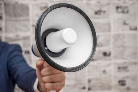 A man holding a megaphone on background of newspapers. News message concept. Banque d'images