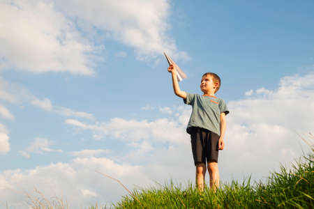 Little boy launches a paper plane into the air. Child launches a paper plane. Happy kid playing with paper airplane.