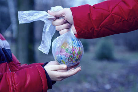Hand of a little child reaching out to take a globe in plastic bag from an adult so he can take care of the earth for his future. Save the earth. World environmental day.