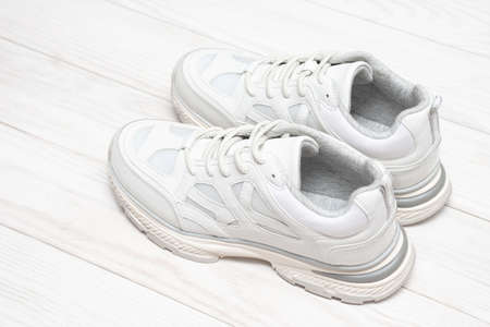 Sneakers on a white wooden background with copy space. Fashionable sneakers on a wooden background. Sport shoes.