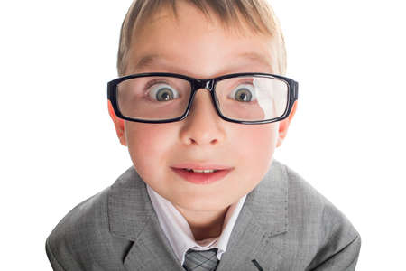 Portrait of a funny child in glasses and a business suit on a white background. Smart child in suit and glasses looking at camera with his big eyes.
