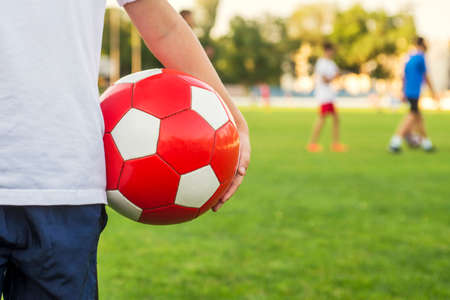 A boy stands on the football field of the stadium and holds a soccer ball against the background of his team or the opposing team. Training or competition concept.
