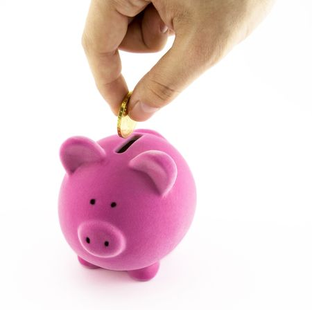 moneybox: Pink piggy bank and hand with coin Stock Photo
