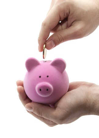 money box: Putting coin into the piggy bank