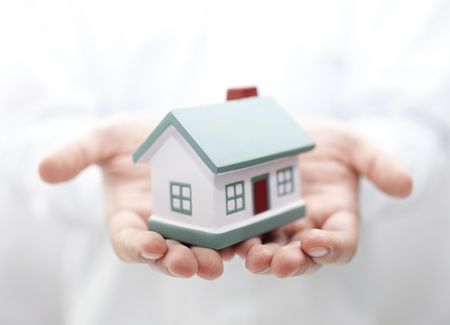 home insurance: House in hands. Shallow DOF