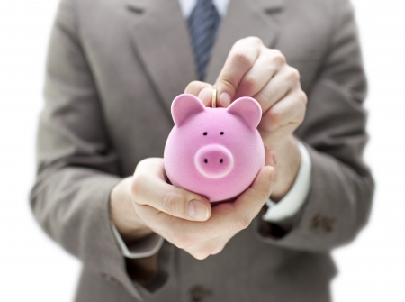 safe deposit box: Businessman putting coin into the piggy bank
