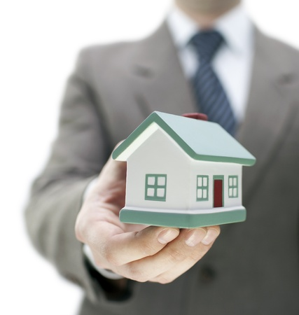 Real estate agent holding a toy house photo