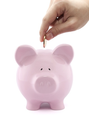 put: Putting coin into the piggy bank Stock Photo