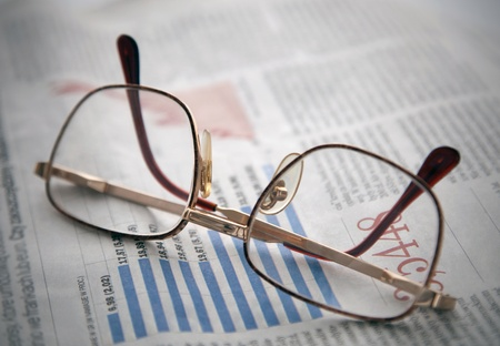 Glasses on a newspaper with financial chart Stock Photo - 10465188
