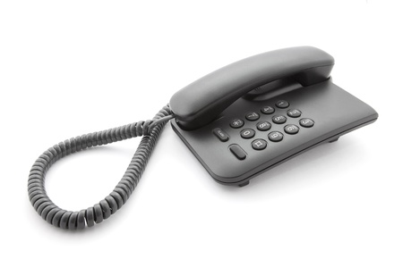 landlines: Black office telephone with soft shadow on white