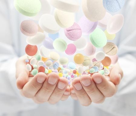pills in hand: Pastillas de colores cayendo en las palmas abiertas Foto de archivo