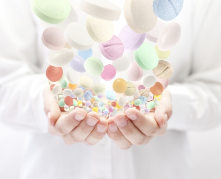Colorful pills falling into open palms photo