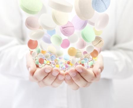pills in hand: Pastillas de colores cayendo en las manos abiertas