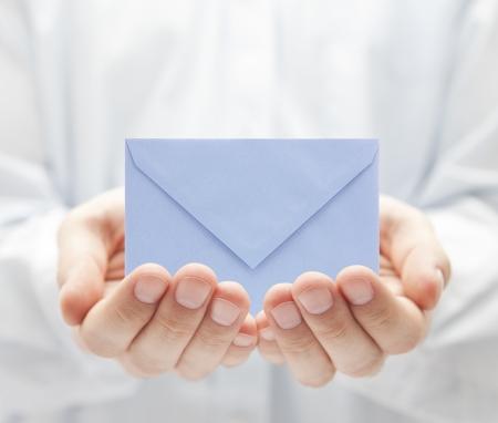 Email: Blauer Papierumschlag in die H�nde Lizenzfreie Bilder