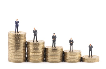 Business figures on stacks of coins