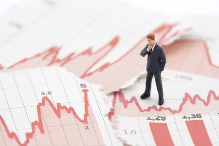 Financial crisis. Figure of businessman on financial charts photo