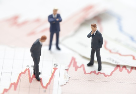 financial crisis: Financial crisis. Figures of businessman on financial charts