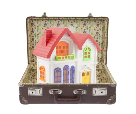 exile: New colorful house in old suitcase with clipping path