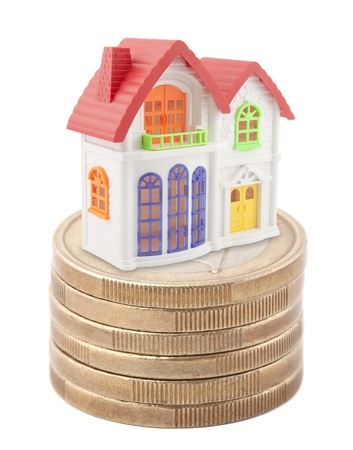 Colorful toy house on stack of euro coins photo