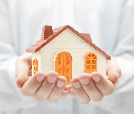 Small orange toy house in hands photo