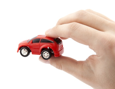 Hand holding a small red car photo