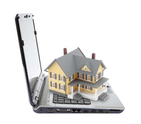 House on laptop isolated on white photo