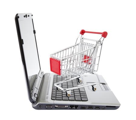Las compras en línea Cesta de la compra con ordenador portátil en blanco