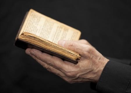 本を持っている老人の手