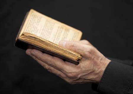 Hands of an old man holding a book Imagens