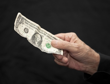 solicitation: One Dollar in old hand   Stock Photo