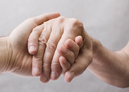 giving hands: Young hand give help to old hand Stock Photo