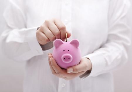 cuenta bancaria: Poner la moneda en la hucha Foto de archivo