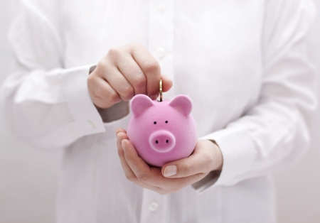Putting coin into the piggy bank Stock Photo
