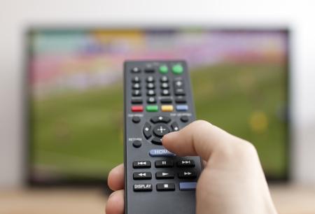 Hand pressing remote control Фото со стока