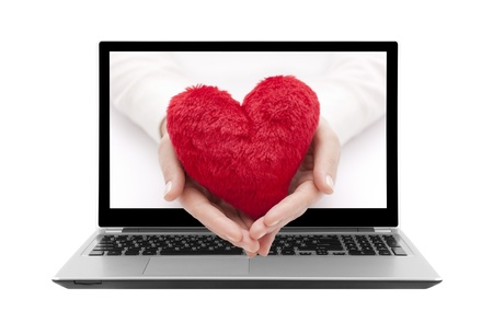 Laptop with red heart in woman hands photo