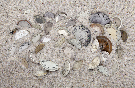 Antique watch faces in the sand  Lost time concept  photo